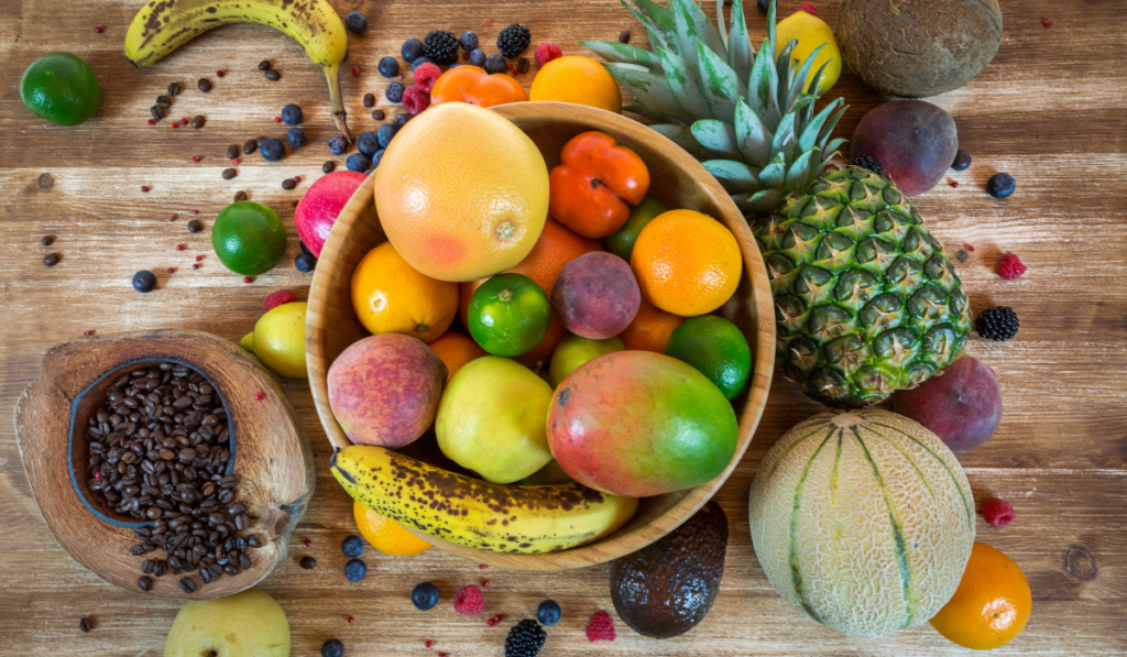 A bowl of fruits on a brown wooden table.