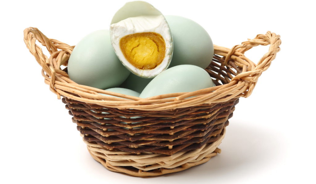 Eggs and an open cooked egg on a wooden basket with white background.