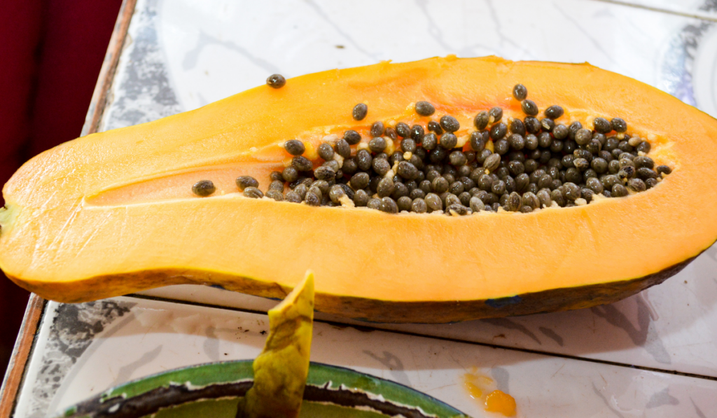 A sliced papaya with its seed on tiled table
