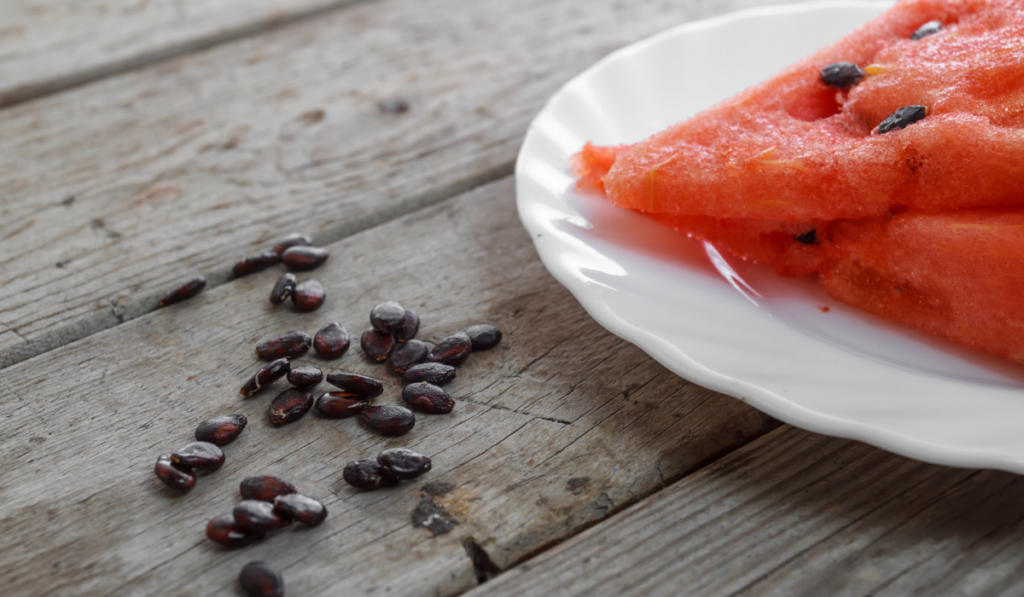 A sliced watermelon on a plate and some seed on the table